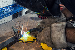 Man weld a metal welding machine in a workshop. Close-up A young man welder wearing a black welding mask and building crochets is weld a metal welding machine in Stock Photos