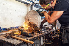Man welder cuts a metal with a circular saw Royalty Free Stock Photo