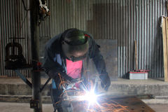Man Welding. A piece of iron on a work table in a shop Royalty Free Stock Photography