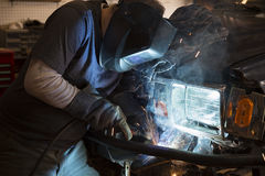 Man welding the bumper of a vehicle Royalty Free Stock Image