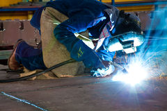 Man welding. Dressed in blue wearing protective clothes and equipment Stock Images