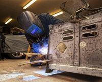 Man Welding Frame. Man welds a frame to a truck Royalty Free Stock Photo