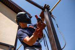 Man welding metal construction at his backyard. Stock Photography