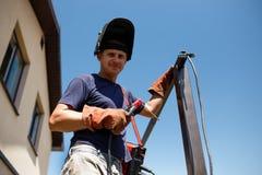 Man welding metal construction at his backyard. Stock Photos