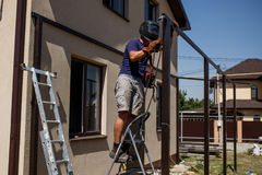 Man welding metal construction at his backyard. Royalty Free Stock Images