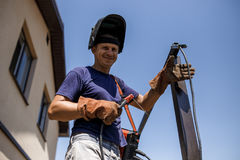 Man welding metal construction at his backyard. Royalty Free Stock Photos