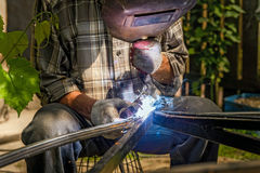 Man welding metal construction at his backyard Royalty Free Stock Images