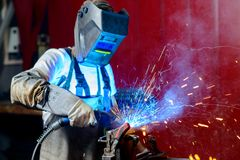 Welder in factory. Man welding metal in the factory Stock Image