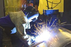 Man welding metal tank. Bright blue sparks and brilliant arcs as a factory worker / artisan concentrates while arc welding a metal tank Stock Photos