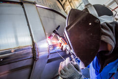 Man welding with reflection of sparks on visor Royalty Free Stock Images