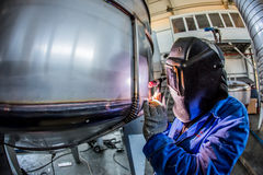 Man welding with reflection of sparks on visor Stock Images