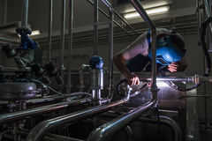 Man welding stainless steel pipes Stock Photo