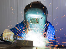 Man welding steel creating many sparks stock photography