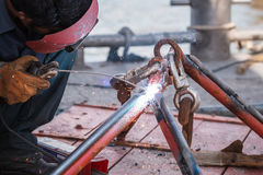 Man welding steel on the part of fishing boat at the harbor Royalty Free Stock Photo