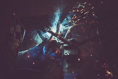 Man welding steel pipe on a work table in an Industrial workshop, producing blue and green smoke, hot sparks. Horizontal photo stock photography