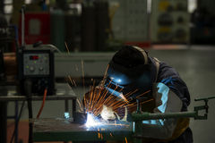 Man welding steel by skill. Men wear protective clothing during work Stock Image