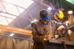 Man welding. Young man with protective goggles welding in a factory Stock Image