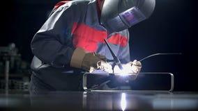 Man welds in full welding gear. Man using welding machine to fix the door handle stock video