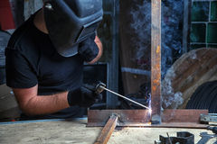 Man welds a metal  arc welding machine. Adult Strong man in a black welding mask cooks a welding machine metal in a dark old garage, working with a welding Royalty Free Stock Photo
