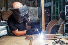 Man welds a metal  arc welding machine. A bald, strong man in a black welding mask is brewing a metal welding machine in a dark old garage, working with a Stock Photo