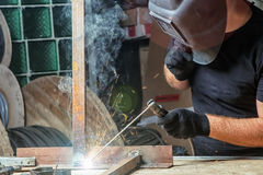 Man welds a metal  arc welding machine. A bald, strong man in black work clothes brewing a metal welding machine in a garage, against a background of a green Stock Images