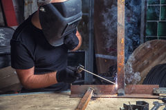 Man welds a metal  arc welding machine. A bald, strong man in black work clothes cooking a metal product with a welding machine in a warehouse, a dark background Stock Photography