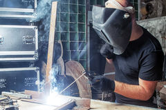 Man welds a metal  arc welding machine. A bald, strong man in black work clothes   welds a metal welding machine  in a warehouse, against a background of a green Royalty Free Stock Photography