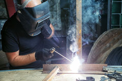 Man welds a metal  arc welding machine. A bald, strong man in black working clothes welds a metal product with arc  welding machine in the warehouse, a dark Stock Images