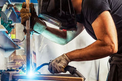 Man welds a metal welding machine. A young brunette man welder in a black T-shirt, in a welding mask and burglars, brews a metal welding machine in the workshop stock photos