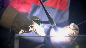 Man welds some metal material. Man using welding machine to fix the door handle stock video footage