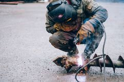 Man welds steell in protective shield. Color of khaki Stock Images