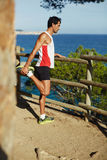 The man went on a morning jog in the mountains, stopped to rest and enjoy the beautiful view of the ocean Stock Image