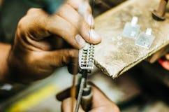 Man werk van de handengoudsmid aangaande een stuk van zilver met een metaalzaag op de het werklijst, sluit omhoog, geselecteerde  stock foto's