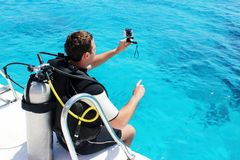 A man in a wet suit, with an aqualung, mask and a balloon. A diver with diving camera in diving gear is preparing to dive.  Royalty Free Stock Image