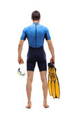 Man in wetsuit holding a diving mask and swimming fins. Full length rear view shot of a man in a wetsuit holding a diving mask and swimming fins isolated on stock image