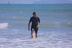 Surfer Man wetsuit ocean. Handsome man in wetsuit swimming in the Pacific Ocean Stock Images