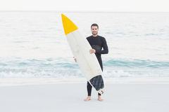 Man in wetsuit with a surfboard on a sunny day. At the beach Royalty Free Stock Photo