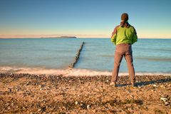 Man on wharf construction and photograph morning sea. Tourist with smart phone above smooth water Stock Image