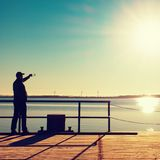 Man on wharf construction and photograph morning sea. Tourist with smart phone above smooth water Stock Photo