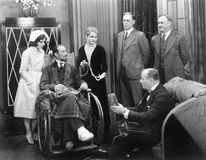Man in a wheel chair with a broken foot and a group of people Stock Images