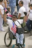 Man in wheel chair holds US flag. In sympathy with hundreds of thousands of immigrants participating in march for Immigrants and Mexicans protesting against Stock Photo