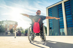 Man on wheel chair. Invalid man sitting on a wheel chair and enjoying a walk outdoors royalty free stock photos