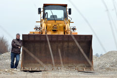 Man at wheel loader. Man stands near big shovel of wheel loader seen from front Royalty Free Stock Photos
