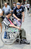 Man in a wheelchair asks for help to passers in the Gothic Quarter. SPAIN, BARCELONA, JUNE, 27, 2015 - Man in a wheelchair asks for help to passers in the Gothic stock photos