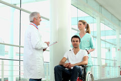 Man in wheelchair being pushed. Man in a wheelchair being pushed by a hospital nurse Stock Photography