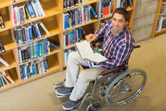 Man in wheelchair by bookshelf in the library Stock Photos