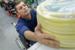 Man in wheelchair buying conduit nylon pipe Royalty Free Stock Image