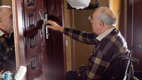 Man in a wheelchair checking his house locks Royalty Free Stock Images