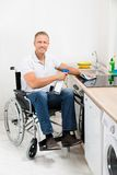 Man on wheelchair cleaning induction stove Royalty Free Stock Photography