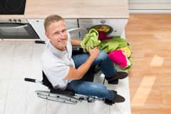 Man on wheelchair with clothes in kitchen room Stock Image